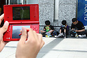 "May 9, 2010 - Tokyo, Japan - Young Japanese play Nintendo's portable video game 'DS' in front of the official Pokemon store in Tokyo on May 9, 2010. Nintendo recently announced that the DS handheld device had become the best selling gaming handheld of all time, with a total of 129 million units sold. The DS 'family' have surpassed the ""Game Boy"" series which hit 118 million over two decades."