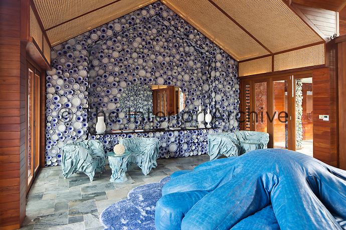 The lobby of the Collectors' Villa at Iniala is dominated by a giant blue leather seat in the shape of an octopus, while the walls are embedded with blue and white plates