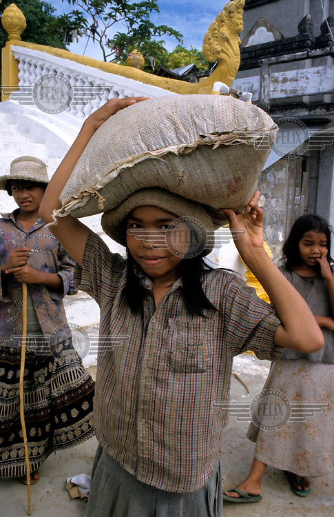 A young girl carrying sandbags to repair a local temple.