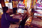 Person playing Sangokushi Taisen card game arcade slot machines in Tokyo, Japan