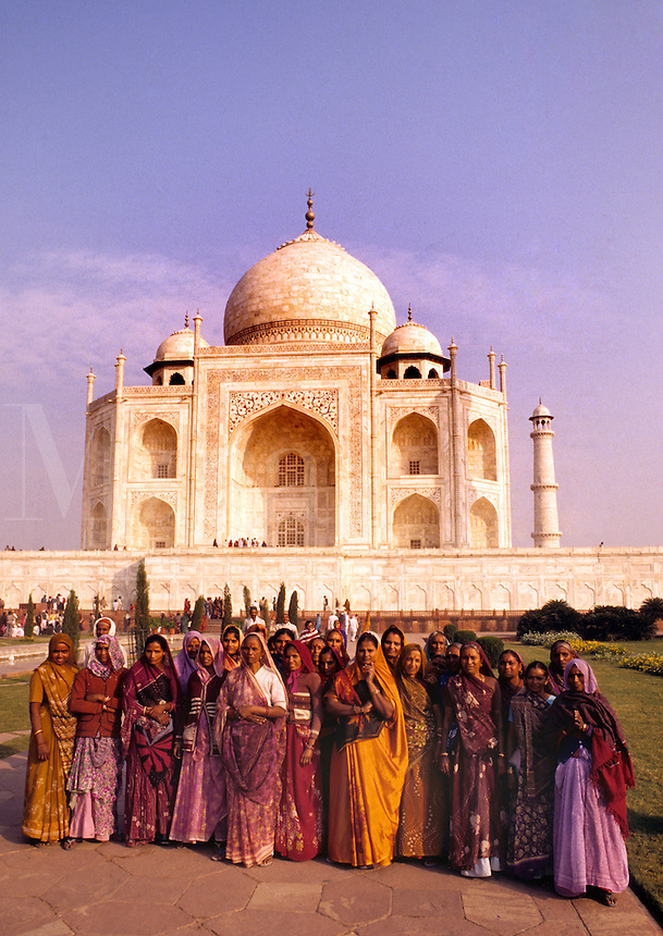 Hindu women in colorful dress in front of the beautiful Taj Mahal monument world famous tomb in Agra India considered the most beautiful building in the world