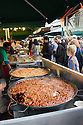 London, UK. 25.10.2014. People looking at food cooking on a food stall at Borough Market, Southwark. Photograph © Jane Hobson.
