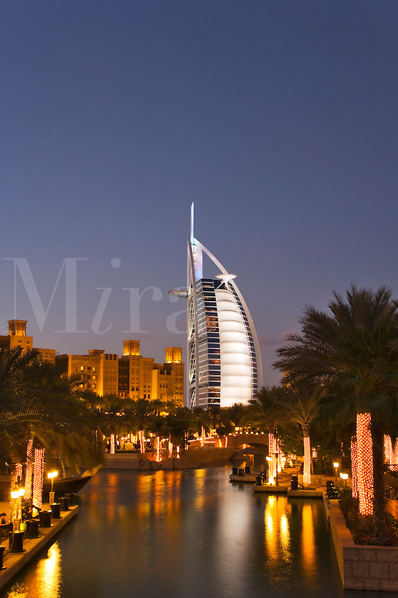 Dubai.  Evening view over Madinat Jumeirah and Mina a?Salam Hotel of Burj al Arab Hotel, architect W.S. Atkins, an icon of Dubai built in the shape of the sail of a dhow, stands on an island off Jumeirah Beach.
