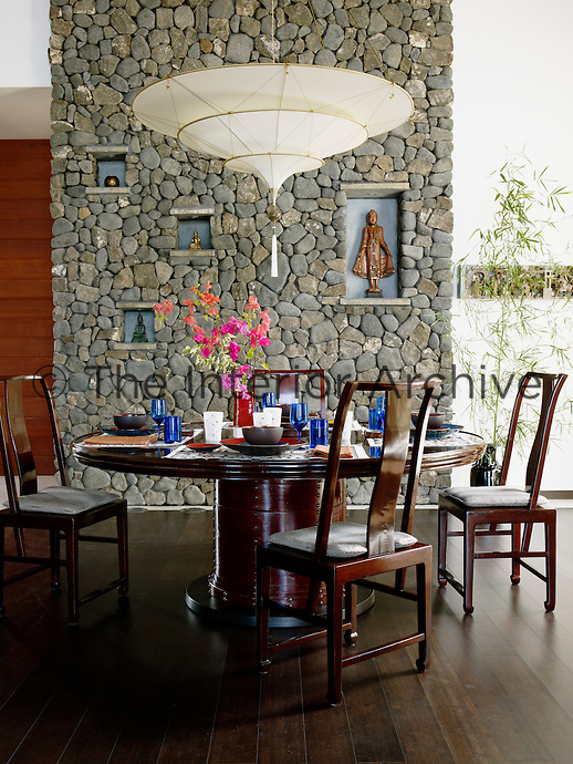 The dining area features a table with a fruit barrel for a base, Chinese chairs, a Fortuny light fixture and a wall of local stone