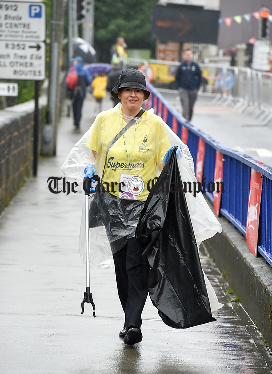 Volunteer Mary Barrett from Darragh doing her bit during a wet final Sunday of the All-Ireland Fleadh in Ennis. Photograph by John Kelly.
