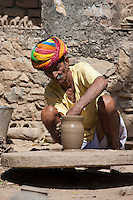 Indian potter in Rajasthani turban works potter's wheel at home making clay pots in Nimaj village, Rajasthan, India