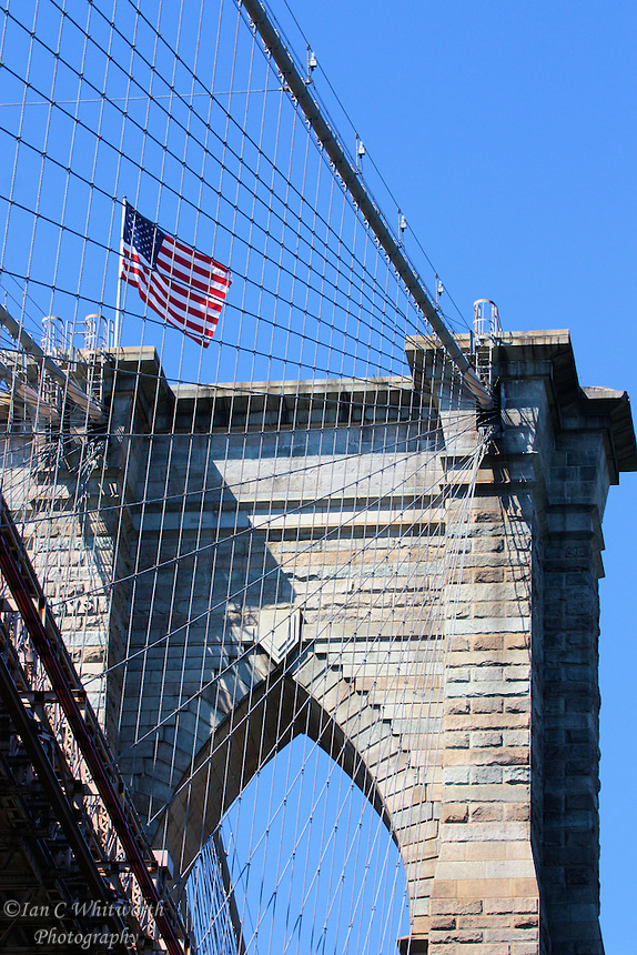 Looking up at the Brooklyn Bridge structure and suspension cables from the East River