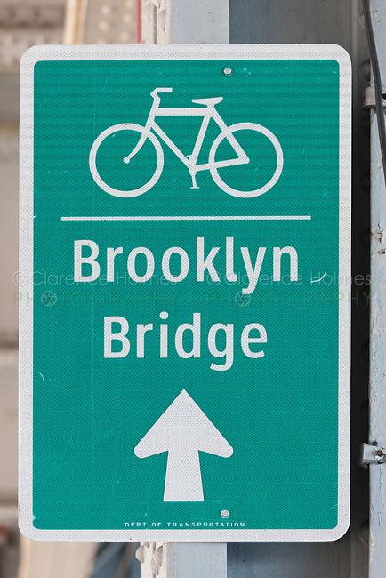 Sign directing cyclists to the bike lane across the Brooklyn Bridge.