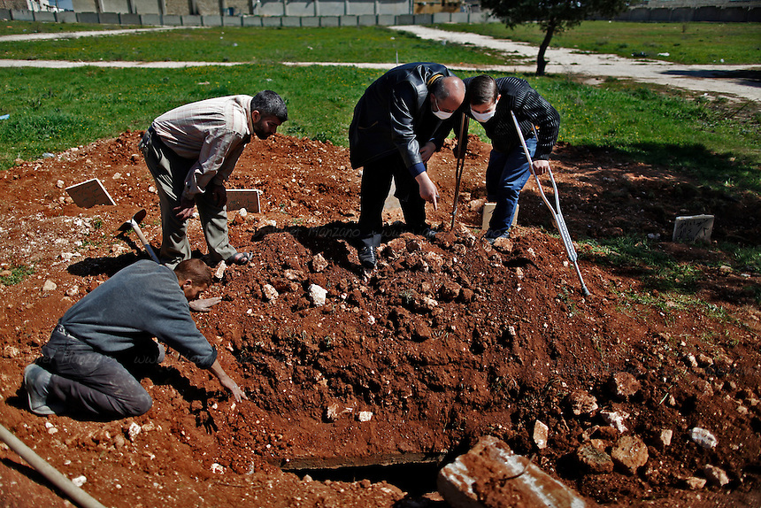 Abo Hamdi (at far right), a former philosophy student at the University of Aleppo looks for his sister's husband at the Islamic cemetery in Aleppo.  Abo Hamdi's brother was killed by a shell in the Bustan Al-Qasr neighborhood of Aleppo (in the same incident that cost Hamdi his right leg). A week later a shell fell on his apartment and killed two of his cousins.  After visiting the Office of the River Martyrs this family asked Hisham if he remembers one of the victims he recently pulled out of the river that displayed a scar on his left forearm - earlier that week they had seen a mugshot of one of the victim's database at Hisham's office that appeared to be Hamdi's brother-in-law. Because of the level of decomposition of the body, Hisham suggested they visit the cemetery where dozens of victims from the river have been laid to rest. The family demanded they exhume two sites in an effort to inspect the corpse and verify if any of them had a scar on his left forearm (a scar that would confirm the identity of Hamdi's brother-in-law). Five bodies were inspected - none of them yielded a positive match.