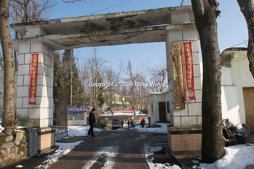 "The main entrance of Man Shan Special Region Hongling Mercury Industry Co. Ltd., one the few factories left in the region run by private enterprise that extraces mercury from ""chu mei"" or touch coal that is imported from Russia, according to the caretaker (the man in black)."