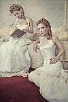 Two young blonde teenage women wearing fancy white vintage corsets sit and read a book.