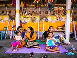 14 JULY 2016 - UBUD, BALI, INDONESIA:  Women and their children relax in front of the alters of their family members who will be cremated in a mass cremation Saturday. Local people in Ubud exhumed the remains of family members and burned their remains in a mass cremation ceremony Wednesday. Thursday was spent preparing for Saturday's ceremony that concludes the cremation. Almost 100 people will be cremated and laid to rest in the largest mass cremation in Bali in years this week. Most of the people on Bali are Hindus. Traditional cremations in Bali are very expensive, so communities usually hold one mass cremation approximately every five years. The cremation in Ubud will conclude Saturday, with a large community ceremony.    PHOTO BY JACK KURTZ