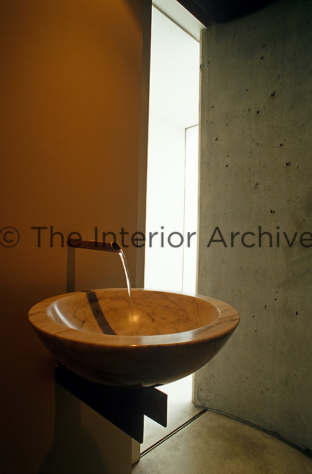 Detail of a circular marble wash basin in a concrete bathroom