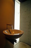 Detail of a circular marble wash basin in a concrete bathroom