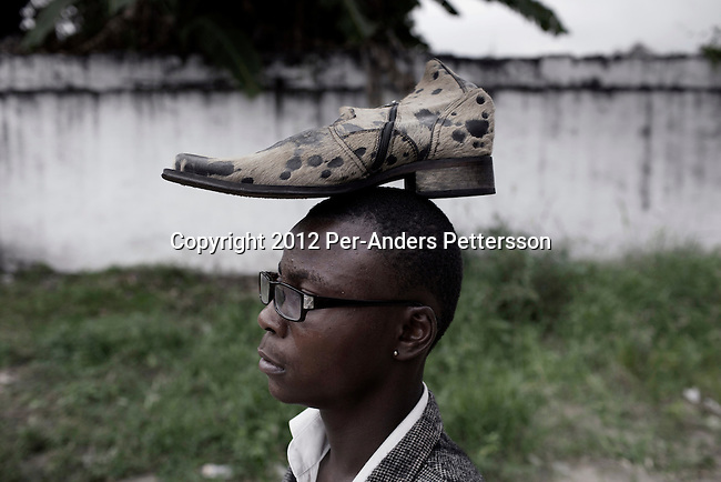 """KINSHASA, DEMOCRATIC REPUBLIC OF CONGO - FEBRUARY 10: A young Sapeur wears a shoe on his head as he parades and shows his designer label clothes while paying their respect to Stervos Nyarcos, the founder of the .kitendi religion., which means clothing in local language Lingala. Nyarcos was known as the leader of the Sape movement, at Gombe cemetery on February 10, 2012 in Kinshasa, DRC. The word Sapeur comes from SAPE, a French acronym for Société des Ambianceurs et Persons Élégants. or .Society of Revellers and Elegant People. and it also means, .to dress with elegance and style"""". Most of the young Sapeurs are unemployed, poor and live in harsh conditions in Kinshasa,  a city of about 10 million people. For many of them being a Sapeur means they can escape their daily struggles and dress like fashionable Europeans. Many hustle to build up their expensive collections. Most Sapeurs could never afford to visit Paris, and usually relatives send or bring clothes back to Kinshasa. (Photo by Per-Anders Pettersson)"""