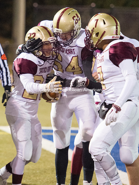 WATERBURY, CT - 25 November 2015-112515EC05--  Sacred Heart's (22) Joel Guzman scores a touchdown against Wilby Friday night and celebrates with (64) Anthony Bonicki and (7) Rashaun Ivester. Erin Covey Republican-American.