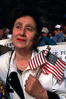 (970522-SWR01)--File Photo -- New York, NY -- A woman with a handful of small American Flags was among thousands of immigrants who gathered in Battery Park, in the shadow of the Statue of Liberty and Ellis Island, for a Rally for Immigrants Rights.  Photo © Stacy Walsh Rosenstock
