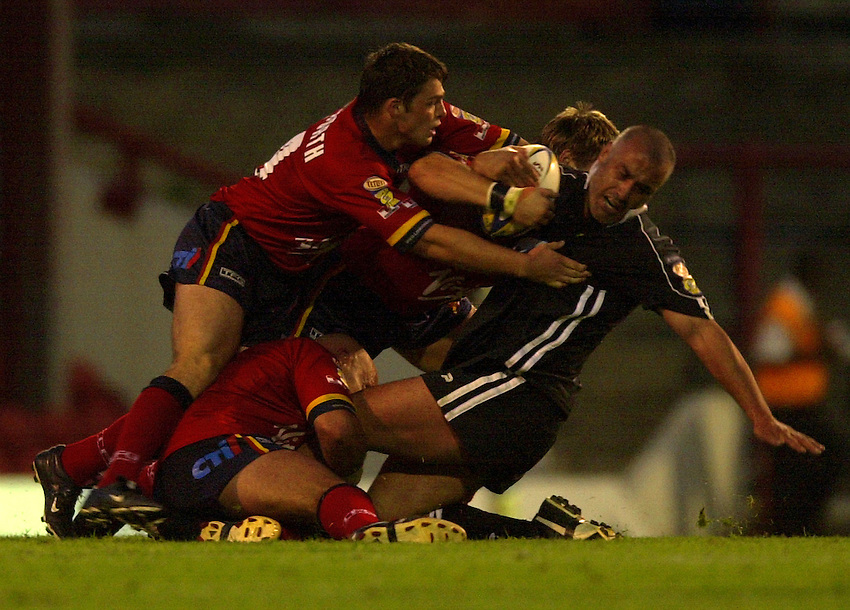 Photo: Richard Lane..London Broncos v Wigan Warriors. Tetleys Super League. 18/07/2003..Quentin Pongia is brought down by the Broncos defence.