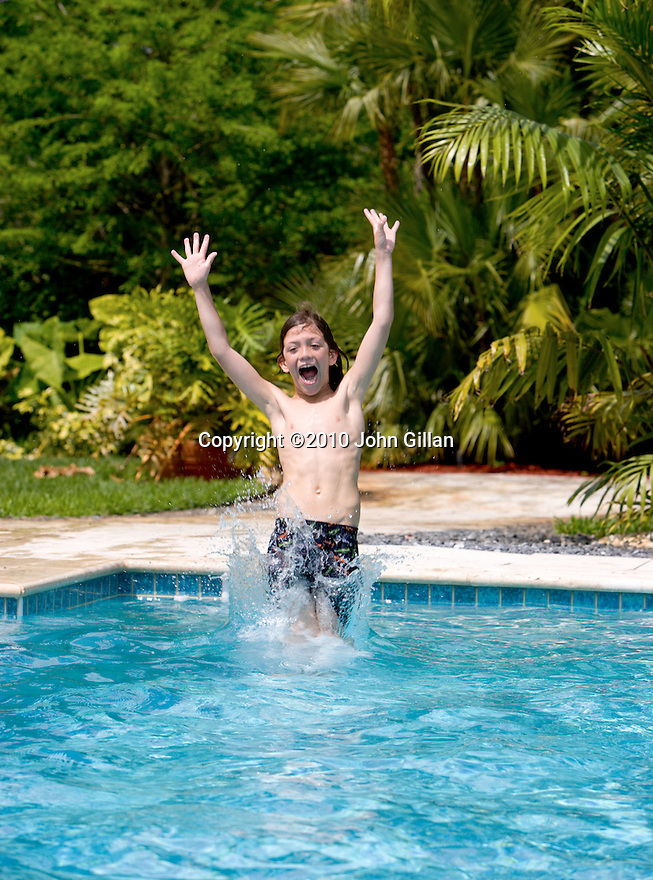 Boy jumping into swimming pool with lush tropical trees in the background. File # WX3P0069