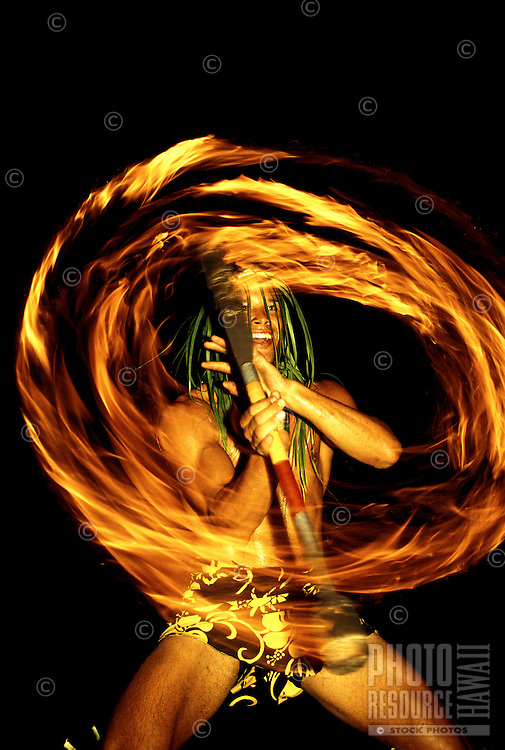 Spectacular Polynesian fire dancer entertains tourists at a luau on the Big Island of Hawaii.