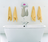Above the free-standing bath yellow towels hang on individual hooks either side of a mirror in the shape of a large daisy