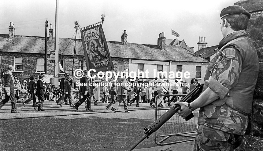 British soldier is discretely vigilant as a Sandy Row flute band and an Orange lodge make their way to join the main procession to The Field at Edenderry on the outskirts of Belfast. 12th July 1974, 197407120389d<br /> <br /> Copyright Image from Victor Patterson, 54 Dorchester Park, Belfast, UK, BT9 6RJ<br /> <br /> Tel: +44 28 9066 1296<br /> Mob: +44 7802 353836<br /> Voicemail +44 20 8816 7153<br /> Email: victorpatterson@me.com<br /> Email: victorpatterson@gmail.com<br /> <br /> IMPORTANT: My Terms and Conditions of Business are at www.victorpatterson.com