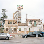 A billboard for Terra Mitica theme park looms over old buildings in Alicante.