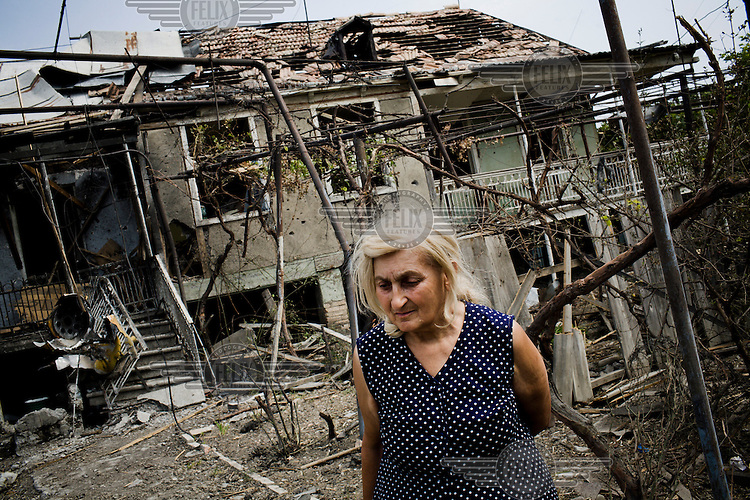 An elderly woman from the ethnic Georgian village of Tkviavi walks to the corner of her house a day after Russian bombers targeted the village. Over half the village was completely destroyed and left many residents completely shellshocked.