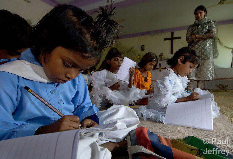 Safina Karamad, left, and other students studying in a school for poor children held in St. Mathew's Church in the Punjab village of Bajasinsingh. This school is sponsored by the Church of Pakistan. The teacher in the background is Nazia Shamim.