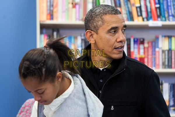 United States President Barack Obama, center, and daughters Sasha, left, and Malia, right, shop in Arlington, Virginia on Small Business Saturday, .November 24th, 2012 .half length side profile black white pink jacket top father dad family.CAP/ADM/CNP/KT.©Kristoffer Tripplaar/CNP/AdMedia/Capital Pictures.