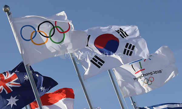 The Olympic flag (L), the South Korean flag (C) as well as the flag of the Pyeongchang 2018 Winter Olympics, waving in the wind in front of the Olympic Stadium in Pyeongchang, South Korea, 07 February 2018. The Pyeongchang 2018 Winter Olympics take place between 09 and 25 February. Photo: Tobias Hase/dpa /MediaPunch ***FOR USA ONLY***