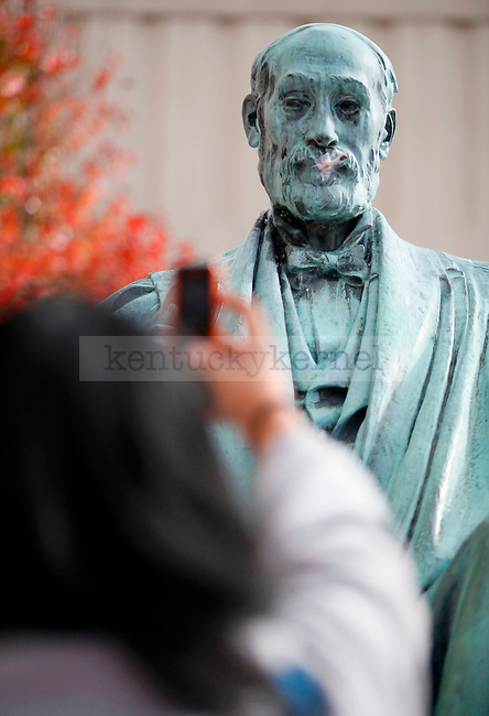 Integrative strategic communications sophomore Kamla Jones takes a picture with her phone of the Patterson statue with a cigarette in his mouth on Thursday. Photo by Zach Brake | Staff