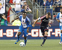 Philadelphia Union midfielder Amobi Okugo (14) works to clear ball as New England Revolution midfielder Chad Barrett (9) defends. In a Major League Soccer (MLS) match, the New England Revolution (dark blue) defeated Philadelphia Union (light blue), 5-1, at Gillette Stadium on August 25, 2013.