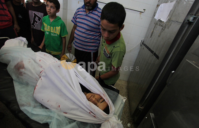 Palestinian relatives mourn arround the body of Ahmed Al-Masri, 14, who witnesses said was killed in an Israeli airstrike, at the morgue of al-Aqsa hospital in Deir Al-Balah town in Central Gaza Strip, August 10, 2014. Palestinian negotiators will remain in Cairo for an urgent meeting with the Arab League on Monday to discuss the Gaza crisis, Egypt's state MENA news agency said. The Palestinian delegation had said it was likely to abandon Egyptian-mediated talks on Sunday unless Israel agreed to return to the table without pre-conditions. Photo by Ramdan El-Agha