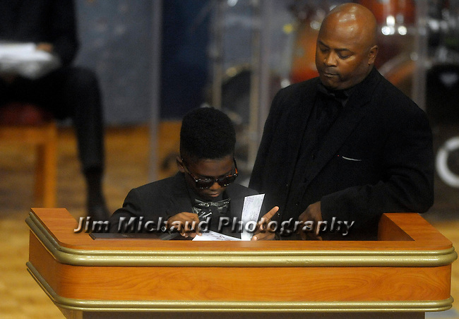Sean Bell with his son Sean Jr. who is a student at the John F. Kennedy Middle School in Windsor,  reads from notes of support to him and his family from his fellow classmates,  firefighter Kevin Bell, during the funeral service, Monday, Oct. 13, 2014, at First Cathedral Church in Bloomfield. Bell was killed at a house fire in last week Hartford. (Jim Michaud / Journal Inquirer)