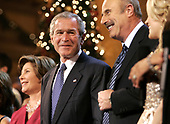 "(L-R) First Lady Laura Bush, President George W. Bush and television talk show host Dr. Phil McGraw sing ""Hark The Herald Angels Sing"" during the finale of the 24th annual ""Christmas in Washington"" pageant December 11, 2005 at the National Building Museum in Washington, DC. The annual holiday musical celebration benefiting the Children's National Medical Center will broadcast on TNT December 14, 2005.  <br /> Credit: Chip Somodevilla / Pool via CNP"