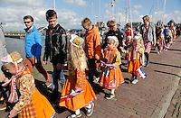 Koningsdag in Marken. Tijdens Koningsdag dragen veel inwoners van Marken klederdracht met oranje accenten. Optocht door het dorp