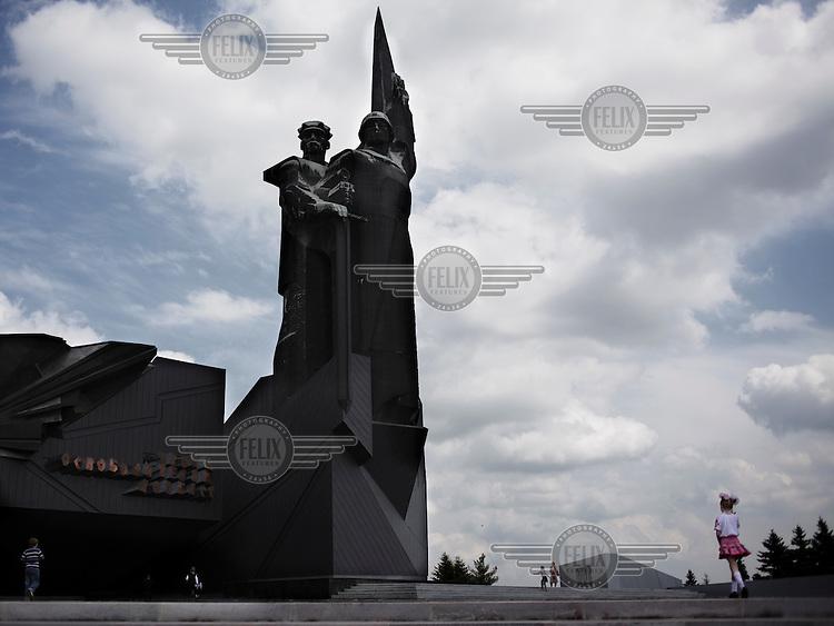 A young girl stands near Donetsk's main war memorial.