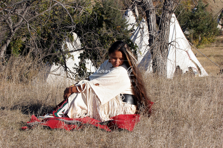 A young Native American Indian Woman portrait sitting on a red blanket