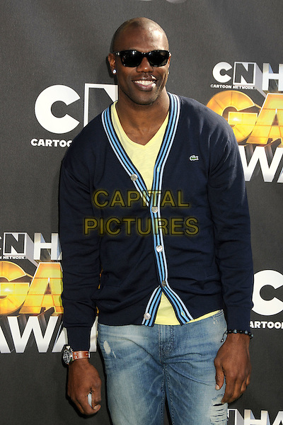 TERRELL OWENS .1st Annual Cartoon Network Hall of Game Awards held at Barker Hangar, Santa Monica, California, USA..February 21st, 2011.half length black blue cardigan sunglasses shades denim jeans.CAP/ADM/BP.©Byron Purvis/AdMedia/Capital Pictures.
