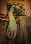 The arm of a sleeping statue in a graveyard
