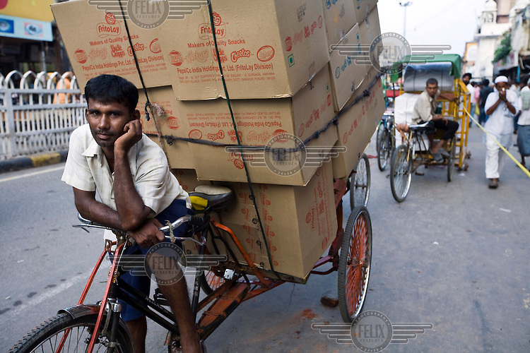 A rickshaw wallah rests on Chadni Chowk with his deliveries.