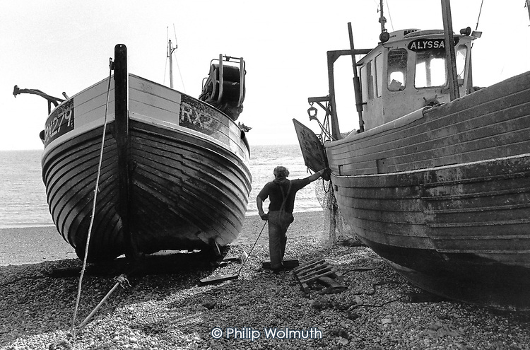 Fisherman by his boat on the beach at Hastings, East Sussex.