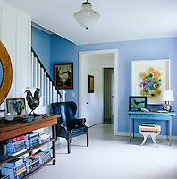 In the spacious entrance hall the walls are painted a fresh lavender blue with pale grey floorboards and a simple staircase leads to the upper floor