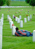 Man age 40 resting by marker on Memorial Day at Fort Snelling Military Cemetery.  Minneapolis Minnesota USA
