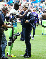 Yaya Toure of Manchester City appears to persuade City manager Manuel Pellegrini to throw his jacket into the crowd at full time during the Barclays Premier League match between Swansea City and Manchester City played at The Liberty Stadium, Swansea on 15th May 2016