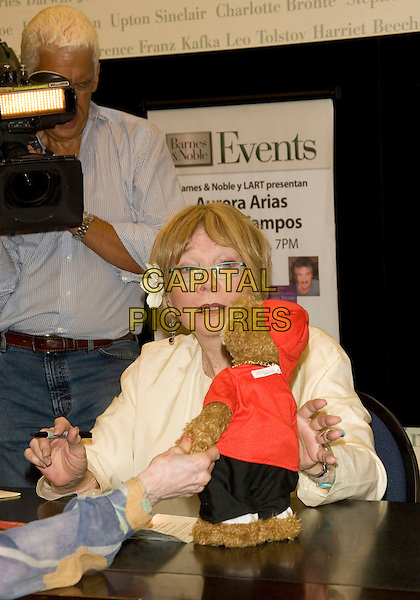 "SHIRLEY MacLAINE.""Sage-ing While Age-ing"" book signing.at the Barnes & Noble -  Lincoln Triangle, New York, NY, USA, .July 22, 2008..half length sitting down cream jacket  flower in hair glasses teddy bear funny toy.CAP/LNC/TOM.©LNC/Capital Pictures"