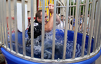 NWA Democrat-Gazette/DAVID GOTTSCHALK   University of Arkansas Police Department Detective David Robertson reacts Tuesday, May 2, 2017, as enters the water after Mohammed Abdulkader hits the lever on a dunking booth on the campus in Fayetteville. The department hosted a Dunk a Cop! and demonstration event to benefit the K9 unit. The UAPD K-9 division plays and active role in keeping students, faculty, staff and fans safe on campus. In addition to their regular patrol duties, Dingo, Orry, Leah and Oakley and their handlers provide standard explosives security and narcotics detection for the University of Arkansas.