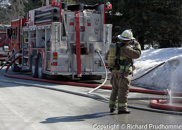 A fire chief stand behind a fire truck at the scene of a fire