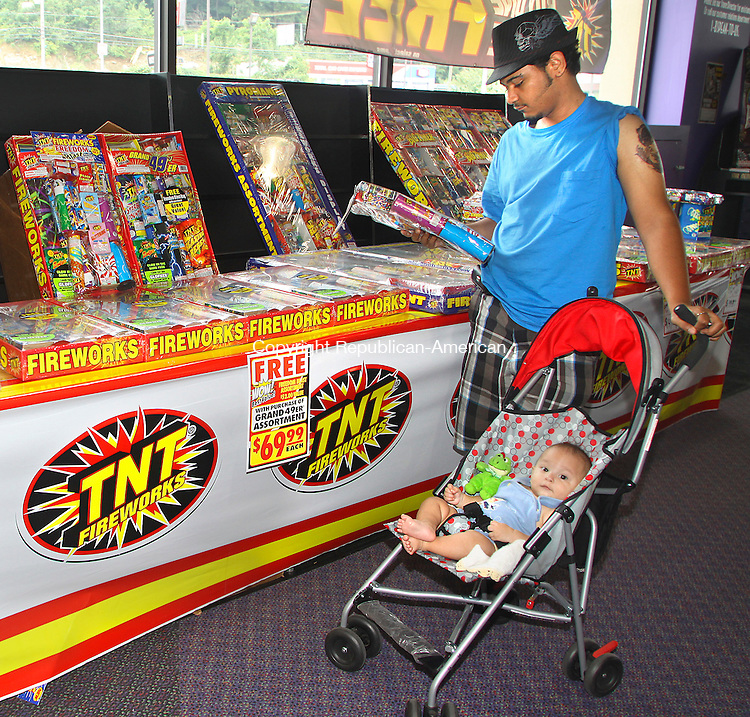 WATERBURY CT.-24  JUNE 2010-062410DA02-  Aristides Reyes of Waterbury and his nephew Angel Torres shop for fireworks at the Waterbury Plaza Thursday. The store is open 7 days a week from 9am-9pm.